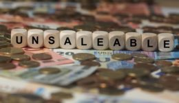 unsaleable - cube with letters, money sector terms - sign with wooden cubes